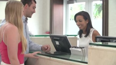Couple Checking In At Hotel Reception Using Digital Tablet — Stock Video