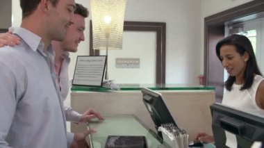 Male Couple Check In At Hotel Reception — Stock Video