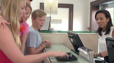 Family Checking In At Hotel Reception Using Digital Tablet — Stock Video