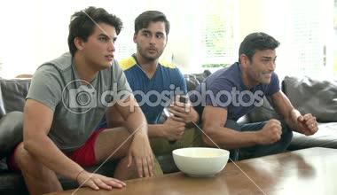 Three Men Sitting On Sofa Watching TV — Stock Video