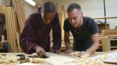 Carpinteiro com aprendiz de lixar madeira — Vídeo stock