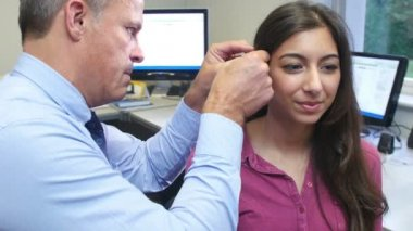Doctor Fitting Female Patient With Hearing Aid — Stock Video