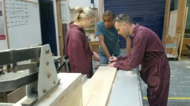 Carpenter Showing Apprentices How To Measure Wood — Stockvideo