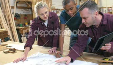 Carpenter With Apprentices Looking At Plans In Workshop — Stock Video