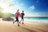 Man and woman running on tropical beach at sunset  — Stock Photo