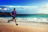 Man running on tropical beach at sunset — Stock Photo