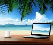 Notebook on table and tropical beach — Stok fotoğraf