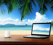 Notebook on table and tropical beach — Stockfoto
