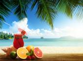 Strawberry cocktail and tropical fruit on the beach — Stock Photo