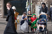 JERUSALEM, ISRAEL - MARCH 15, 2006: Purim carnival. Ultra Orthodox  woman with children crossing the road.Children dressed in costumes — 图库照片