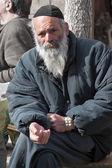 JERUSALEM, ISRAEL - MARCH 15, 2006: Purim carnival. Portrait of a tramp begging. An elderly man in a black jacket, kippa and beard — Stock Photo