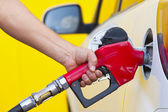 Pumping gas at gas pump. Closeup of man pumping gasoline fuel in — Stock Photo