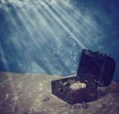 Chest with coins under water — Stock Photo