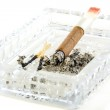 Cigarette butt with red lipstick in the ashtray. — Stock Photo #65543087