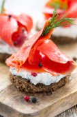Sandwich of black bread, cheese with herbs and red salmon. — Stock Photo
