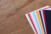 Color paper on wood background — Stock Photo