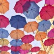 Colorful umbrellas over old building and sky — Stock Photo #55271623