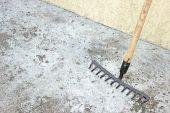 Rake tool over concrete background — Stock fotografie