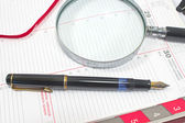 Fountain pen and magnifying glass on personal organizer — Stock Photo
