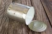 Open empty tin can on wooden background — Stock Photo