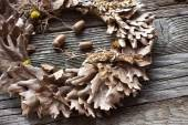 Wreath of oak leaves and acorns on wooden background — Stock Photo