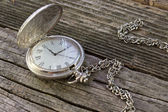 Old pocket watch with chain on wooden background — Stock Photo