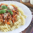 Fusilli pasta with bolognese sauce on kitchen table — Stock Photo #80877336