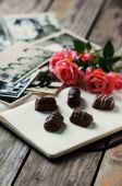 Photoalbum with pink rose and chocolate — Stock Photo