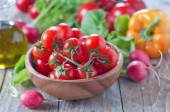 Tomatoes in bowl and vegetables — Stock Photo