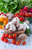 Mushrooms in a wooden bowl and vegetables — Stock Photo