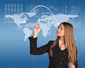 Beautiful businesswoman in suit presses finger virtual map of the world — Stock Photo