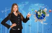 Beautiful businesswoman in suit finger points to Earth with buildings — Stock Photo