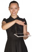 Beautiful girl in dress holding tablet and covers it — Stock Photo