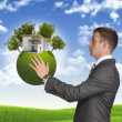 Businessman hold Earth with small house and trees — Stock Photo #54227087
