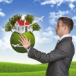 Businessman hold Earth with small house and trees — Stock Photo #54227109