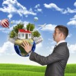 Businessman hold Earth with small house and trees — Stock Photo #54227203