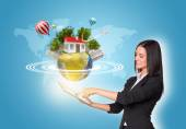 Women using digital tablet and Earth with buildings — Stock Photo