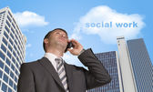 Businessman talking on the phone. Cloud with words social work — Stock Photo