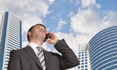 Businessman talking on the phone. Skyscrapers and clouds — Foto de Stock