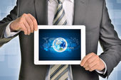 Man hands using tablet pc. Image of Earth on screen — Stock Photo