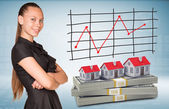 Businesswoman and dollar packs with row houses — Stock Photo