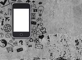 Smart phone on concrete floor with various social icons — Foto de Stock