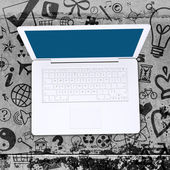 Laptop on concrete floor with various social icons — ストック写真