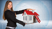 Businesswoman smiling and holding house in hand — Stock Photo