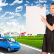 Businesswoman holding empty paper. Industrial zone, buildings and road with car — Stock Photo #56892649