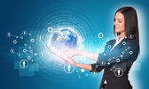 Women using digital tablet. Earth with figures and network — Stockfoto
