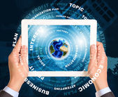 Man hands using tablet pc. Earth and business words on touch screen — Stock Photo