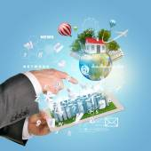 Man hands using tablet pc. Business city on touch screen. Earth with buildings near computer — Stock Photo