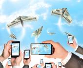 Hands holding smart phones and shoot video as flying paper plane of dollars — Photo