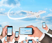 Hands holding smart phones and shoot video as flying airplane — Fotografia Stock